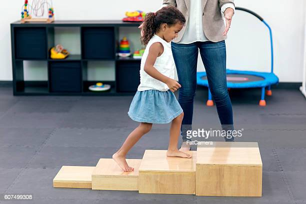 Young ethnic child walking up steps in therapy