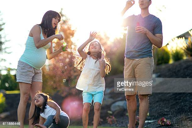 Young ethnic family blowing bubbles in their backyard