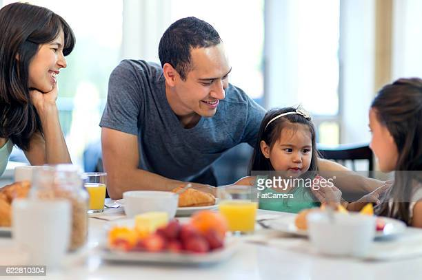 Young ethnic family eating a healthy breakfast together