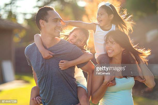 Young ethnic family holding their daughters and laughing together