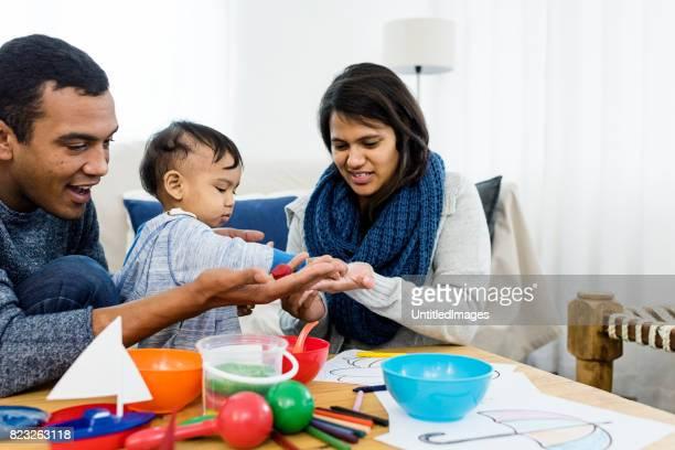 Jonge etnische gezin met baby plezier