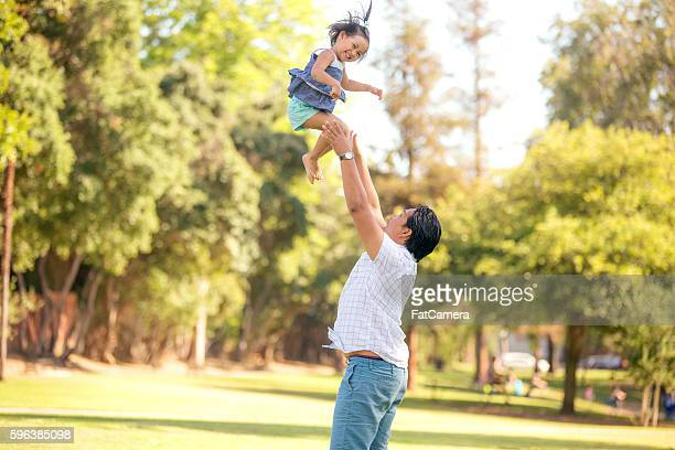 Young ethnic father tossing his daughter in the air