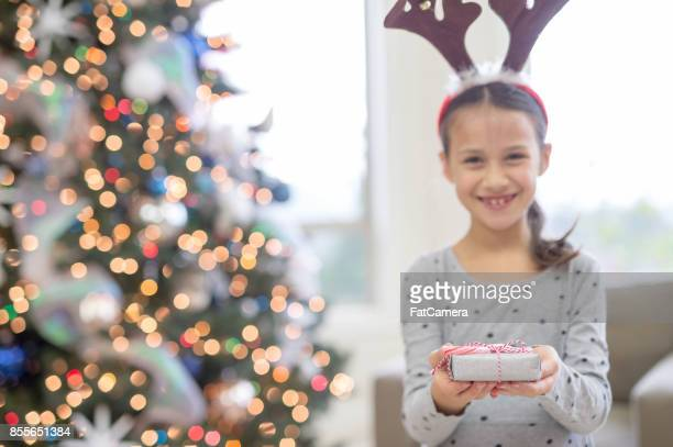 A young ethnic girl delightedly holds open a wrapped present