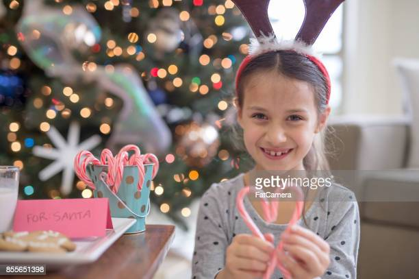 A young ethnic girl delightedly holds up a pair of candy canes in the shape of a heart