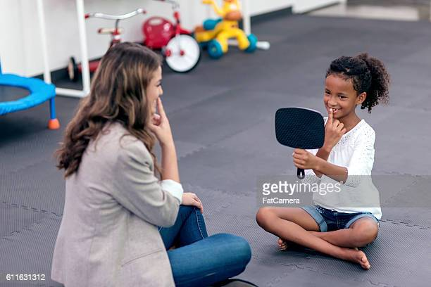 Young ethnic girl looking in mirror during speech therapy