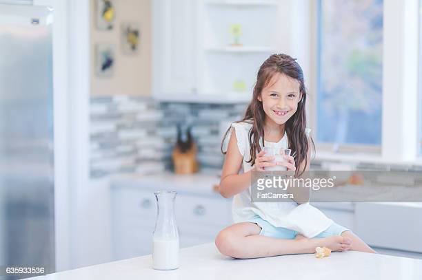 Young ethnic latino girl drinking milk while sitting