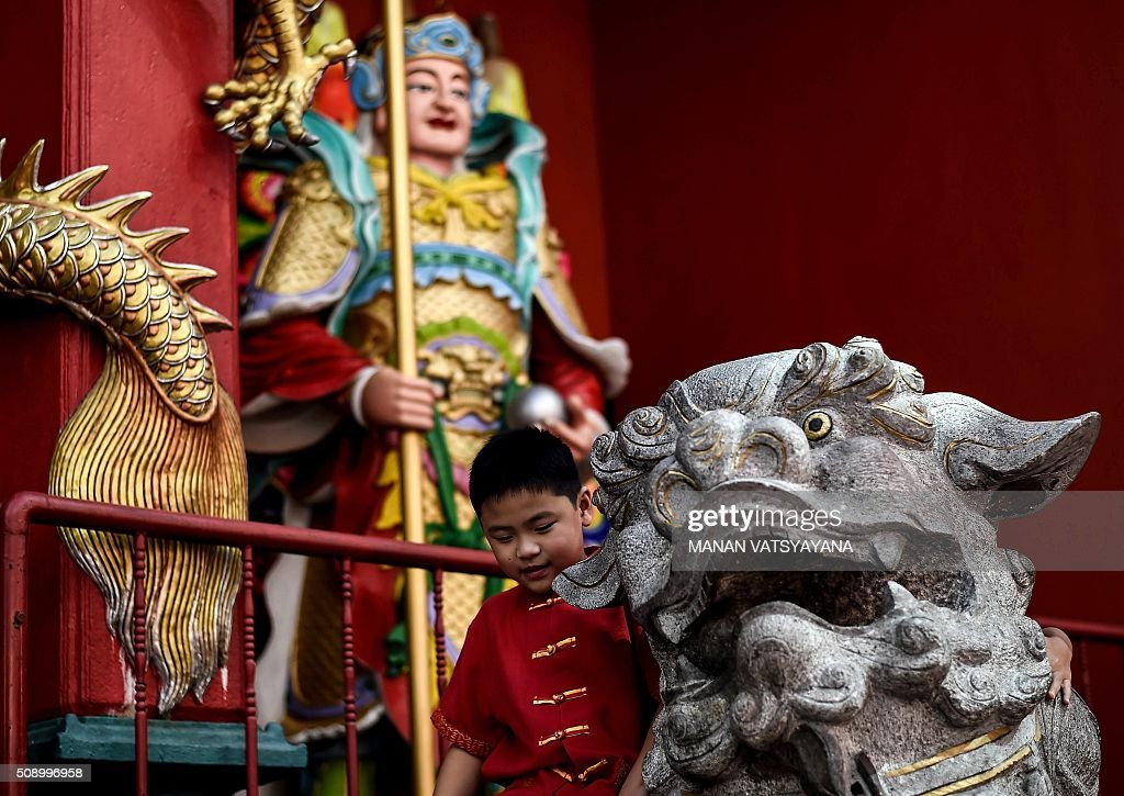 A young ethnic Malaysian-Chinese boy dressed in a traditional outfit plays on a statue at the Guan Di Temple on the first day of the Lunar New Year in Kuala Lumpur's popular Chinatown area on February 8, 2016. Some 25 percent of Malaysia's 29 million people are ethnic Chinese and celebrate the Lunar New Year, this year marking the Year of the Monkey. AFP PHOTO / MANAN VATSYAYANA / AFP / MANAN VATSYAYANA
