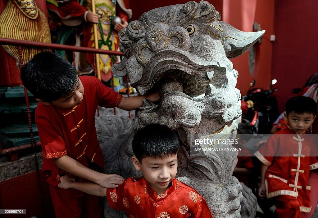 Young ethnic Malaysian-Chinese boys dressed in traditional outfits play on a statue at the Guan Di Temple on the first day of the Lunar New Year in Kuala Lumpur's popular Chinatown area on February 8, 2016. Some 25 percent of Malaysia's 29 million people are ethnic Chinese and celebrate the Lunar New Year, this year marking the Year of the Monkey. AFP PHOTO / MANAN VATSYAYANA / AFP / MANAN VATSYAYANA