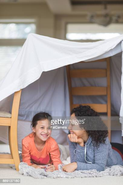 A Young Ethnic Mom and Her Daughter Lay Underneath a Blanket Fort and Talk About LIfe