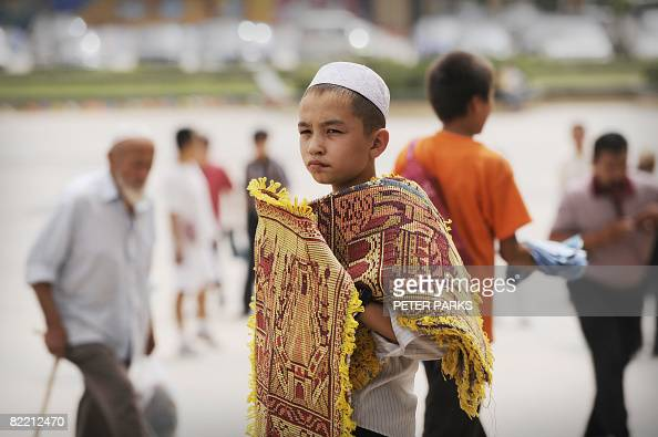 A young ethnic Uighur sells prayer mats for Friday prayers outside the Id Kah Mosque on August 8 2008 in Xinjiang's famed Silk Road city of Kashgar...