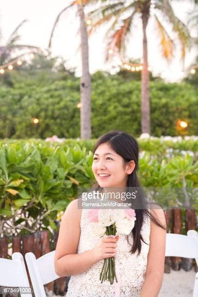 Young Eurasian Woman Holding Bridal Bouquet at Tropical Beach Wedding