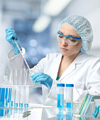 Young female tech or scientist loads liquid sample into test tube with plastic pipette. Shallow DOF, focus on the face