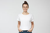 Young european woman standing with hands in pockets, wearing blank white tshirt with copy space for your logo or text, isolated on grey background