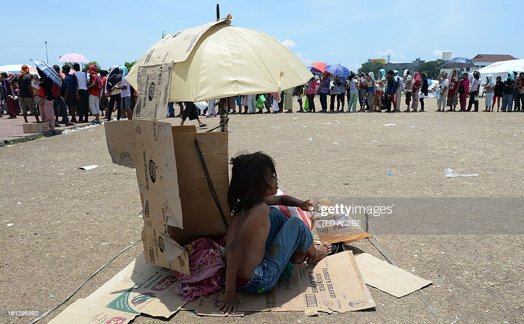 A young evacuee, one of the thousands affected by the stand-off between Philippine government forces and Muslim rebels, shelters from the scorching heat as others queue up for food distribution at an evacuation centre inside a sports complex in Zamboanga, on the southern Philippine island of Mindanao on September 20, 2013. Philippine security forces killed eight Muslim rebels on September 20 as they hunted the remnants of a guerrilla force hiding in homes of the major city and believed to be holding hostages.