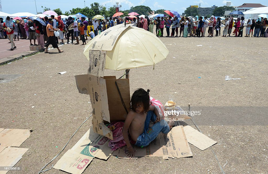 A young evacuee, one of the thousands affected by the stand-off between Philippine government forces and Muslim rebels, shelters from the scorching heat as others queue up for food distribution at an evacuation centre inside a sports complex in Zamboanga, on the southern Philippine island of Mindanao on September 20, 2013. Philippine security forces killed eight Muslim rebels on September 20 as they hunted the remnants of a guerrilla force hiding in homes of the major city and believed to be holding hostages. AFP PHOTO / TED ALJIBE