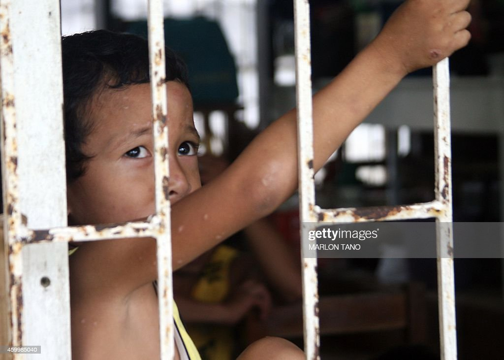 A young evacuee peers from a window at an evacuation center in Tacloban City central Philippines on December 5 ahead of the landfall of Typhoon...