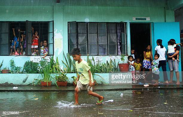 A young evacuee wades through flooded school grounds while others look on from a school building being used as an evacuation center in the city of...