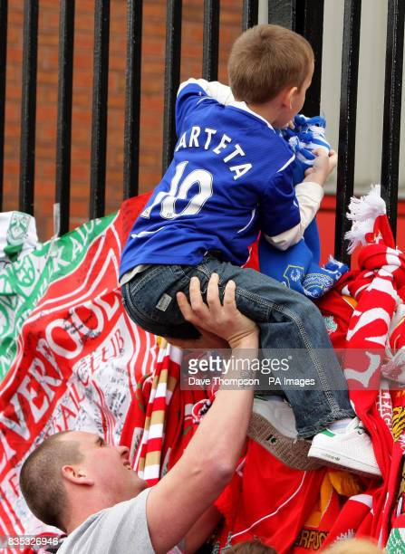 A young Everton fan is lifted up as he ties a scarf to the Shankly Gates at Anfield before the official memorial service at Liverpool's Anfield...