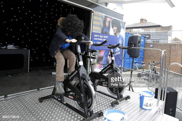 A young Everton fan wearing a Marouane Fellaini rides an exercise bike to raise money on the Everton Roadshow stage