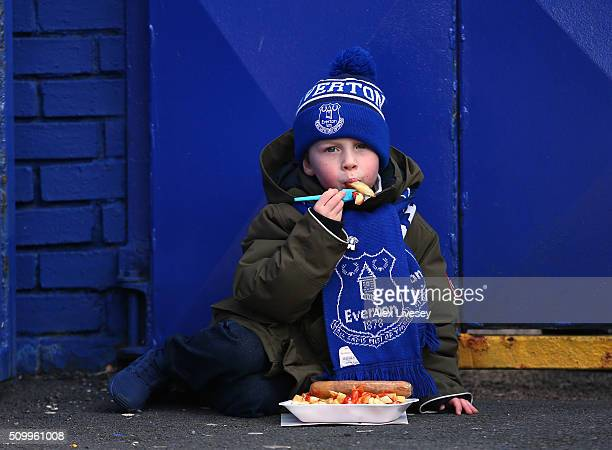 A young Everton supporter eats chips outside Goodison Park prior to the Barclays Premier League match between Everton and West Bromwich Albion at...