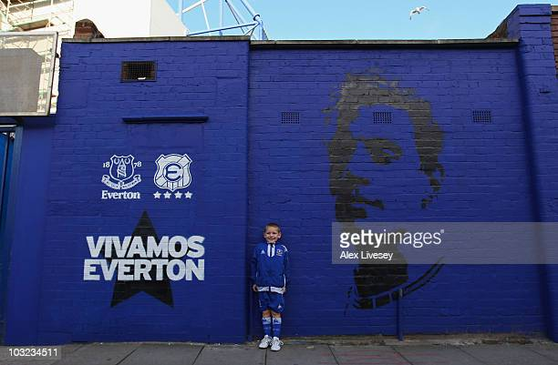 A young Everton supporter stands next to a mural outside Goodison Park prior to the preseason friendly match between Everton and Everton Chile at...