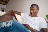 young excited and surprised young black African American man in disbelief and shock face expression networking with laptop computer lying at home living room couch with opened mouth