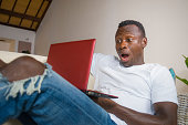 young excited and surprised young black afro American man in disbelief and shock face expression networking with laptop computer lying at home living room couch with opened mouth