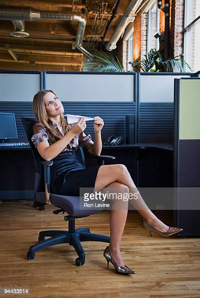 Young executive holding paper airplane in office