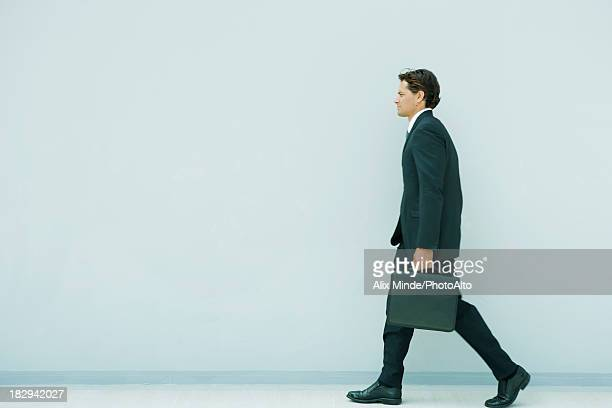 Young executive walking briefcase, side view