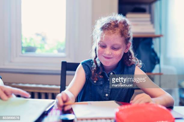 Young expressive redhead girl doing school homework at home.