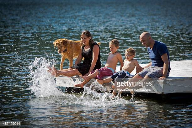 A young family and their pet siting on a dock by the lake