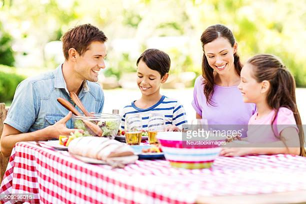 Young Family At Outdoor Lunch Table