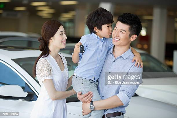 Young family buying car in showroom