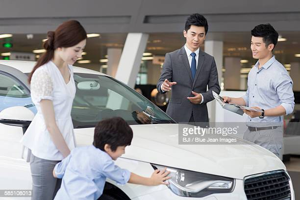 Young family choosing car in showroom