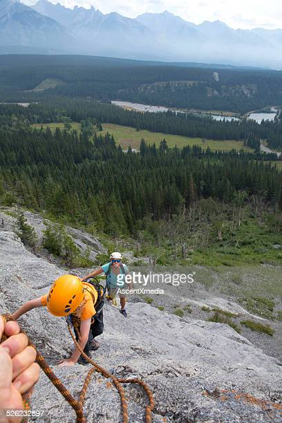 Young family climb cliff above valley, mountains