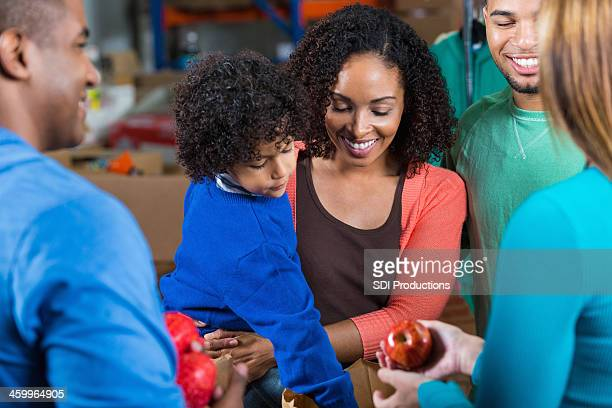 Young family donating or receiving donations at food bank