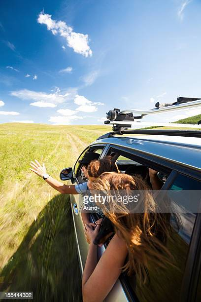 young family driving car in field