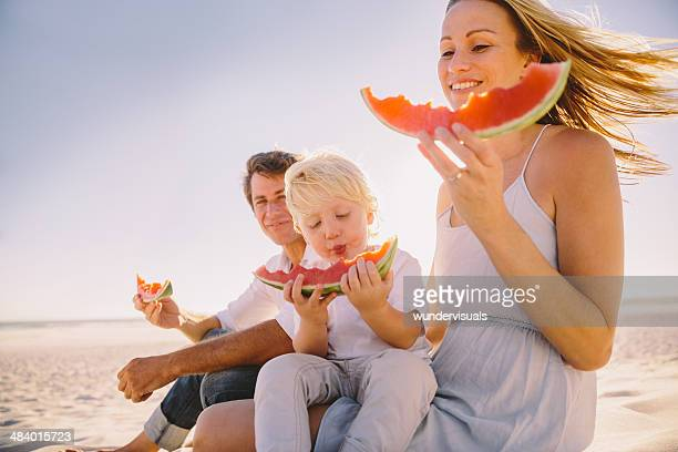 Young family eating watermelon on beach