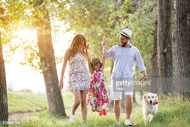 Jeune famille profiter d'une belle journée avec un chien