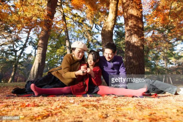 Jeune famille bénéficiant d'automne sous érable japonais