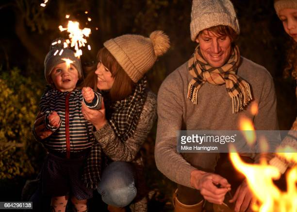 Young family enjoying sparklers on cold winters night