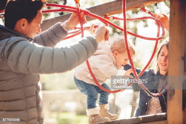Young Family Enjoying Togetherness in the Playground