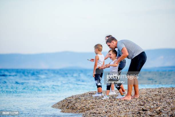 Young Family Enjoying Vacation on Seaside