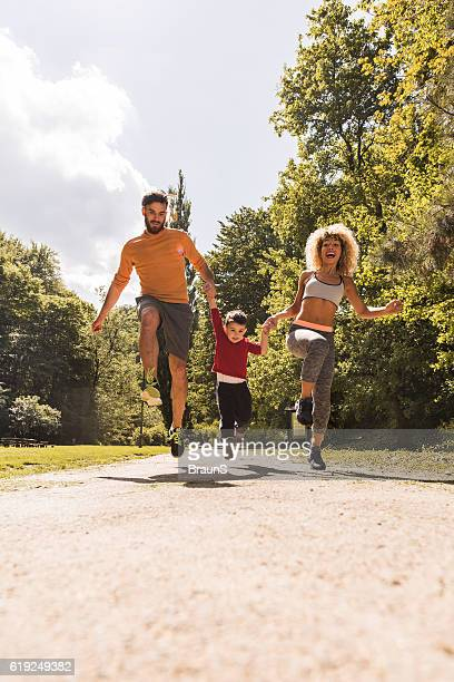Young family exercising jumps together in the park.