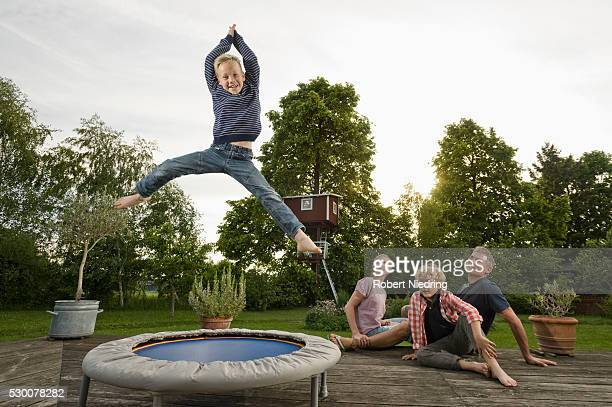 Young family garden boy jumping trampoline