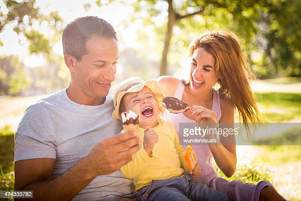 Familia joven feliz comer helados juntos en un parque