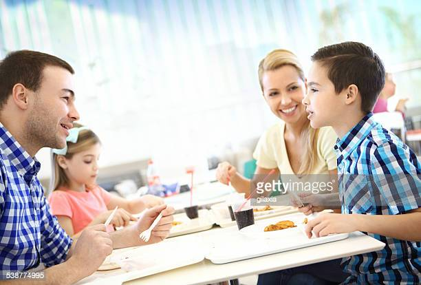 Young family having lunch in restaurant.