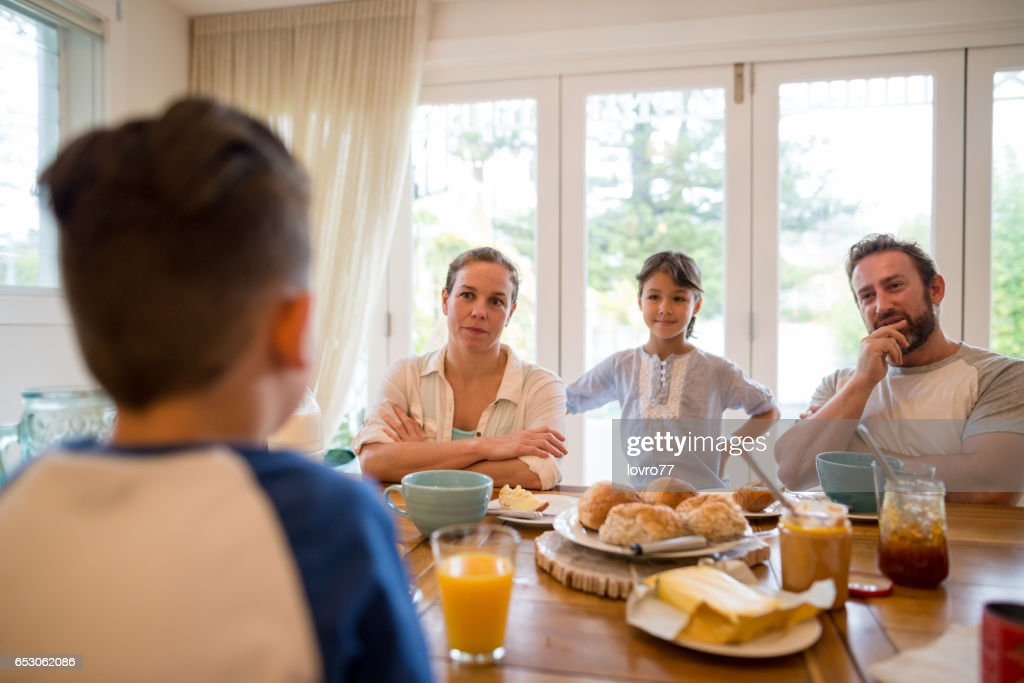Young family having pleasant conversation during breakfast in the dining room : Stock-Foto