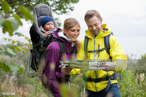 young family hiking, looking at the map together