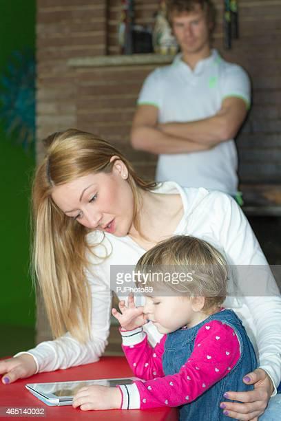 Jeune famille dans le conflit pour tablette numérique